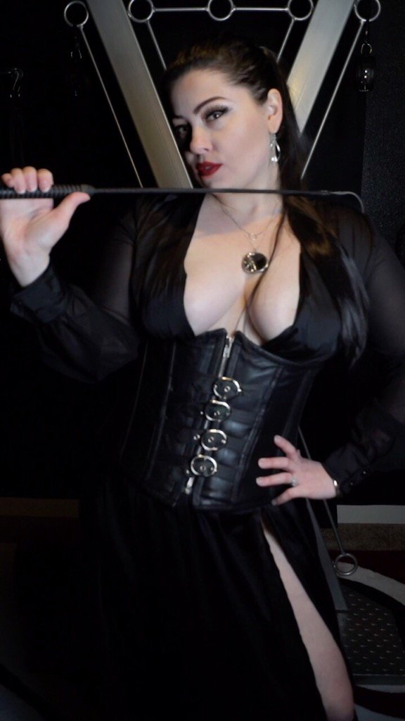 Dominatrix in a leather corset, holding a crop, standing in front of a BDSM cross